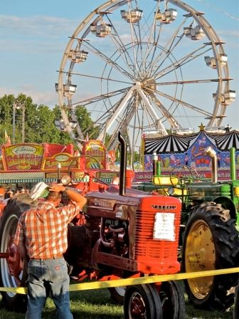 Carnival rides in background and tractor and farmer in the foreground
